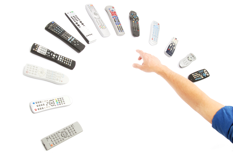 A man's hand reaching for a remote control